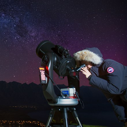 Couple looking through telescopes during a Stargazing tour at Skyline Queenstown.