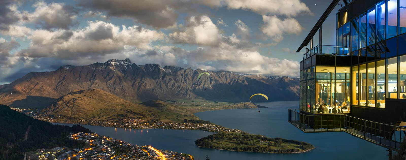 Skyline Queenstowns, Stratosfare Restaurant overlooking paragliders and Queenstown as the sun sets.
