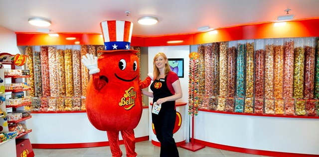 Jelly Belly staff member standing with the Jelly Belly mascot.
