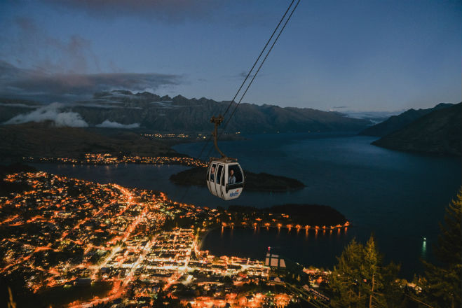 Riding the Skyline Queenstown Gondola just after sunset with the lights of Queenstown in the background.