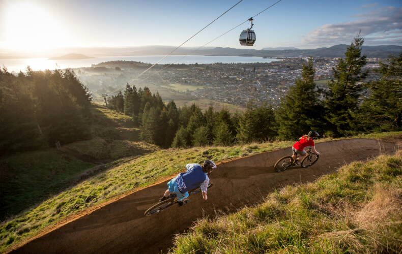 Two bikers riding riding on the gravity park overlooking Rotorua and the Skyline Gondola on a sunny day.
