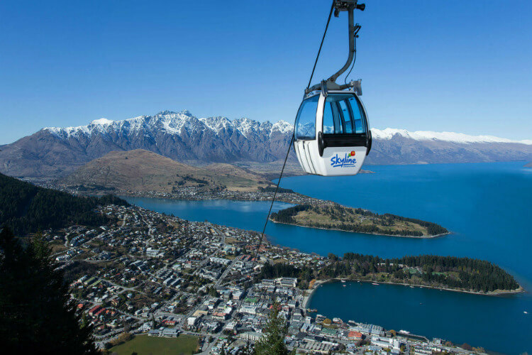 A Skyline Queenstown Gondola on a sunny day, with views of Queenstown and Lake Wakatipu behind.