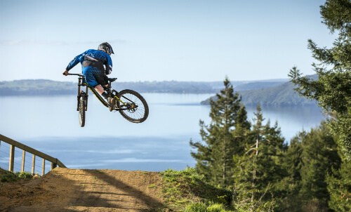 Skyline Rotorua Mountain Biker does a tail whip over a jump.