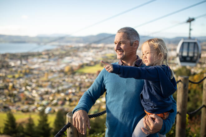 A Father And Daughter Looking At The Views From Skyline Rotorua With A Gondola Passing Behind Them.