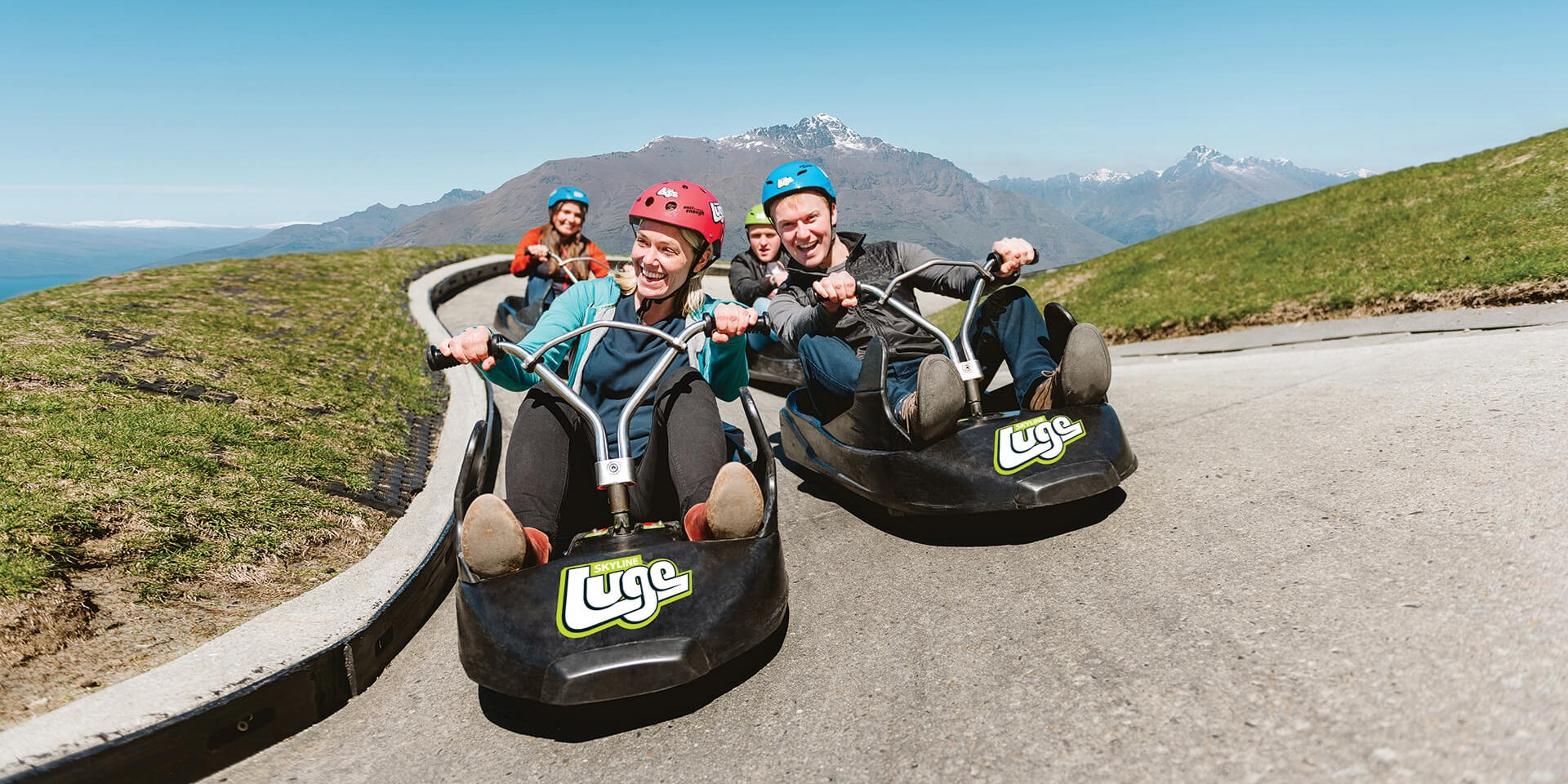 Friends enjoy the luge on a sunny day at Skyline Queenstown.